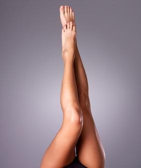 Piękne kobiece nogi po depilacji. zdjęcie na szarym tle