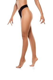 Piękne kobiece nogi, pośladki i brzuch na białej ścianie