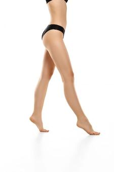 Piękne kobiece nogi, pośladki i brzuch na białym tle na białej przestrzeni