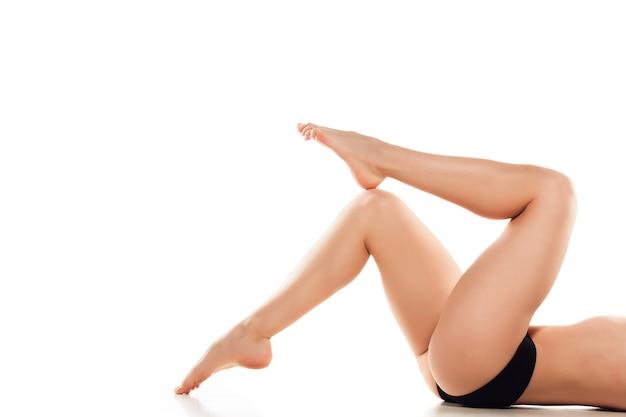 Piękne kobiece nogi, tyłek i brzuch na białym tle na białej ścianie. koncepcja uroda, kosmetyki, spa, depilacja, leczenie i fitness. wysportowane i wysportowane, zmysłowe body o zadbanej skórze w bieliźnie.