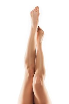 Piękne kobiece nogi, tyłek i brzuch na białym tle na białej ścianie.