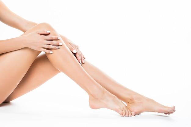 Piękne kobiece nogi, tyłek tył ciała na białym tle nad białą ścianą leżącą na podłodze z długimi nogami, spa beauty i koncepcja pielęgnacji skóry.