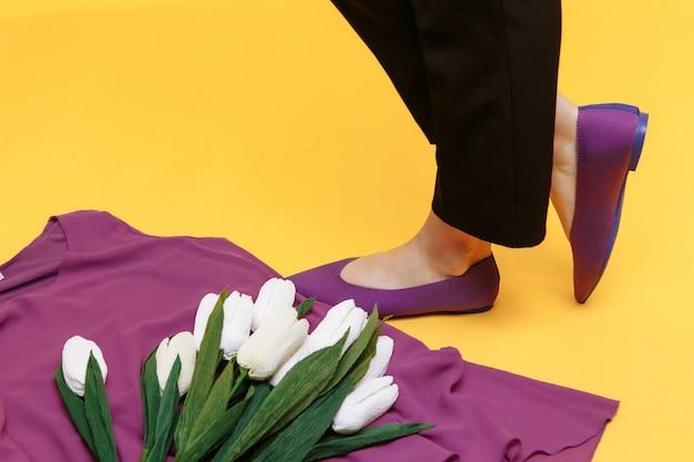 Piękne kobiece nogi ubrane są w stylowe fioletowe płaskie buty. fioletowe sandały