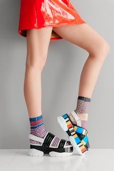Piękne kobiece nogi w niedopasowanych modnych skarpetach stojących w dwóch różnych modnych sandałach z wysokim klinem na białej powierzchni. dziwna młoda dziewczyna w czerwonej spódnicy na sobie letnie stylowe buty z wysoką podeszwą.
