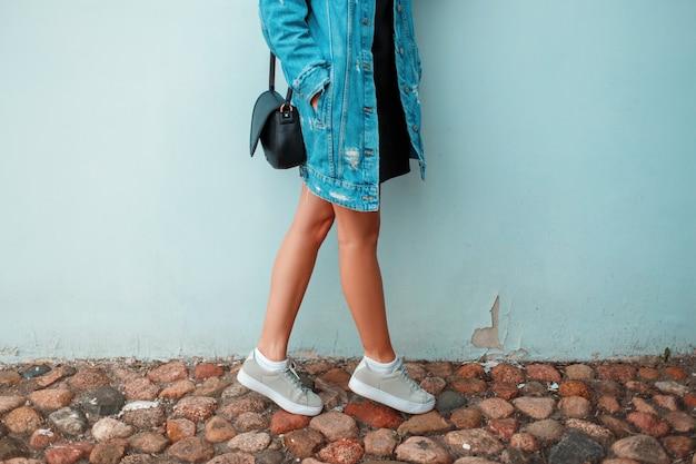 Piękne kobiece nogi w stylowe trampki. modna odzież dżinsowa