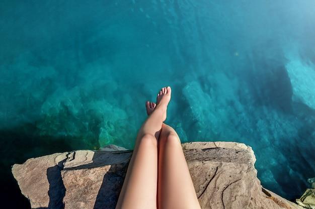 Piękne kobiece nogi w wodzie jeziora. młoda kobieta siedzi na kamieniu na jeziorze. czas letni. koncepcja podróży