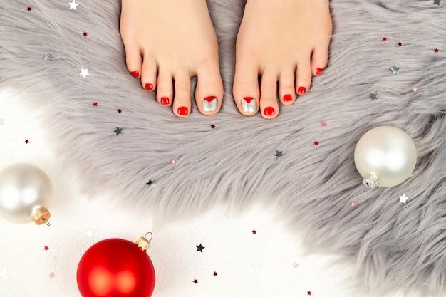 Piękne kobiece nogi ze świątecznym wzorem paznokci na szarym puszystym dywanie