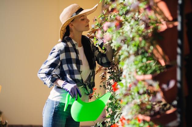 Piękne kobiece ogrodnik podlewania roślin w ogrodzie w upalny letni dzień. koncepcja ogrodnictwa.