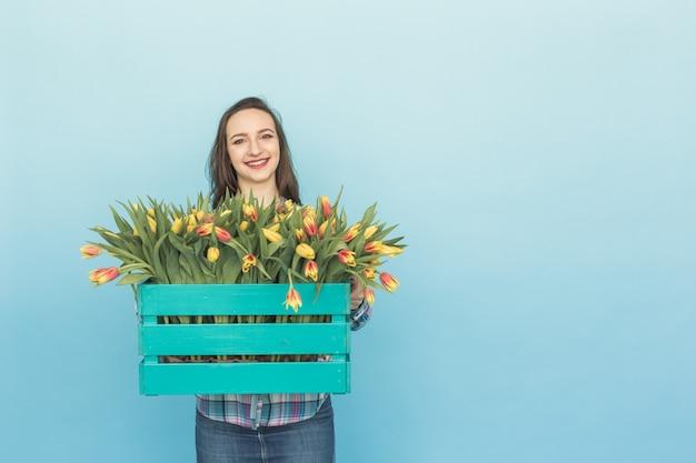 Piękne kobiece ogrodnik trzymając pudełko z tulipanami na niebieskim tle