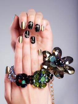 Piękne kobiece paznokcie z kreatywnym manicure i biżuterią