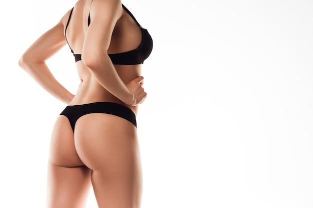 Piękne kobiece plecy i tyłek na białym tle na białej ścianie. koncepcja uroda, kosmetyki, spa, depilacja, leczenie i fitness. wysportowane i wysportowane, zmysłowe body o zadbanej skórze w bieliźnie.