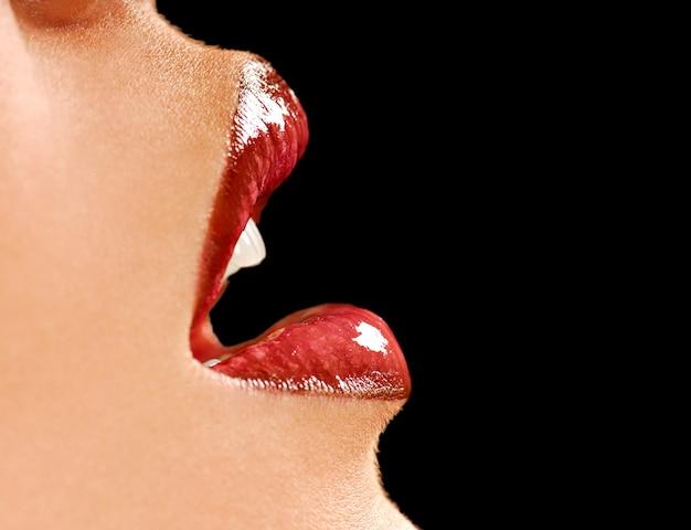 Piękne kobiece usta. błyszcząca szminka. czarne tło. zdrowa skóra.
