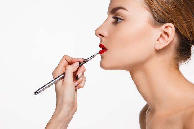 Piękne kobiece usta makijażem i pędzlem na białym tle. proces pracy artysty makijażu