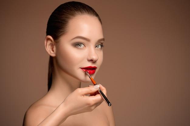 Piękne kobiece usta makijażem i pędzlem