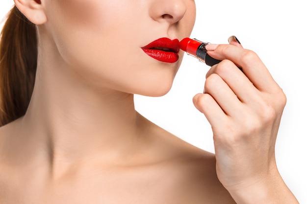 Piękne kobiece usta z makijażem i czerwoną pomadą na białym tle. proces pracy artysty makijażu