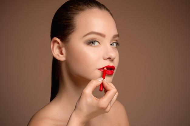 Piękne kobiece usta z makijażem i pędzlem na białym. proces pracy wizażysty