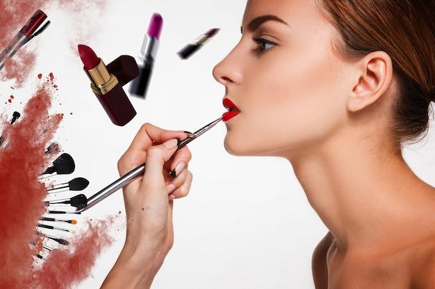 Piękne kobiece usta z makijażem i pędzlem na białym