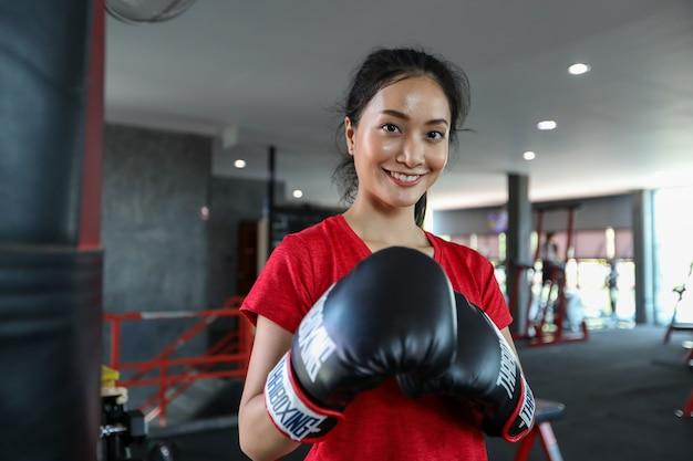 Piękne kobiety azjatyckie bokserki szczęśliwe i zabawne boks fitness i wykrawanie worek z noszeniem rękawic bokserskich.