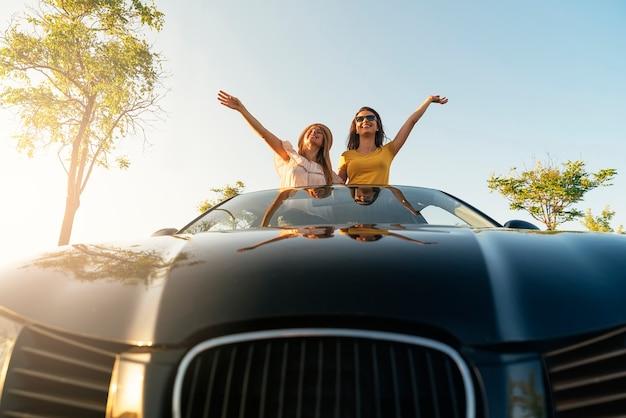 Piękne kobiety bawią się w samochodzie. przyjaciele i koncepcja podróży.