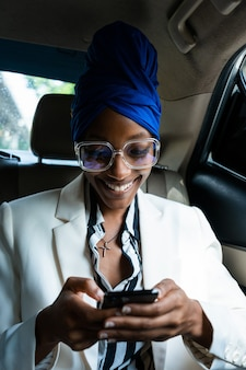 Piękne kobiety biznesu jadące na lotnisko, wyjeżdżające na podróż służbową. używanie smartfona do nawiązywania połączenia telefonicznego