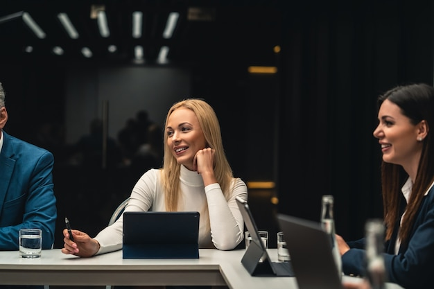 Piękne kobiety biznesu siedzące przy stole na konferencji biznesowej