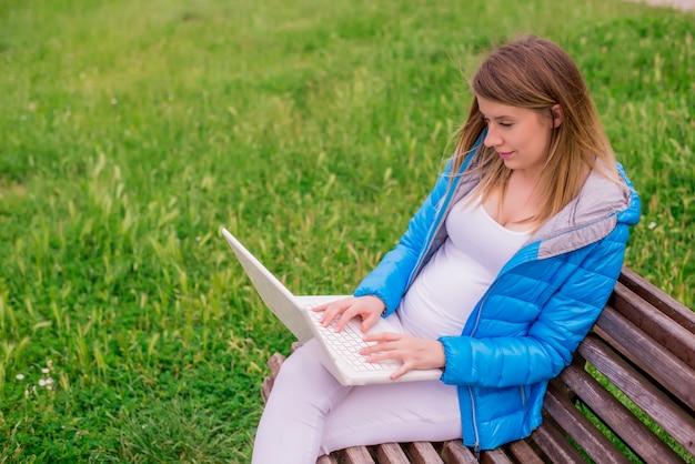 Piękne kobiety ciężarne siedzi na stanowisku przy użyciu komputera przenośnego na zewnątrz.