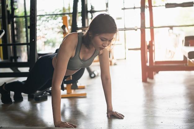 Piękne kobiety ćwiczenia push up na siłowni, koncepcja fitness sport
