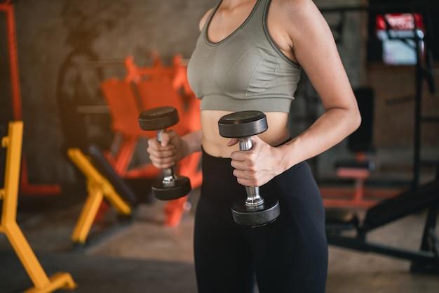 Piękne kobiety ćwiczenia z hantlami na siłowni, koncepcja fitness sport