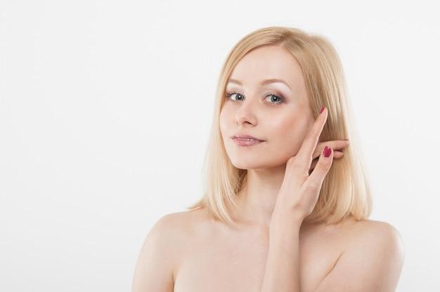 Piękne kobiety dotyka jej twarzy ręką. kobieca twarz o zdrowej skórze. młoda blondynka z nagim makijażem. moda uroda portret z naturalną skórą