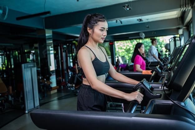 Piękne kobiety fitness przygotowują się do biegania na bieżni w siłowni.