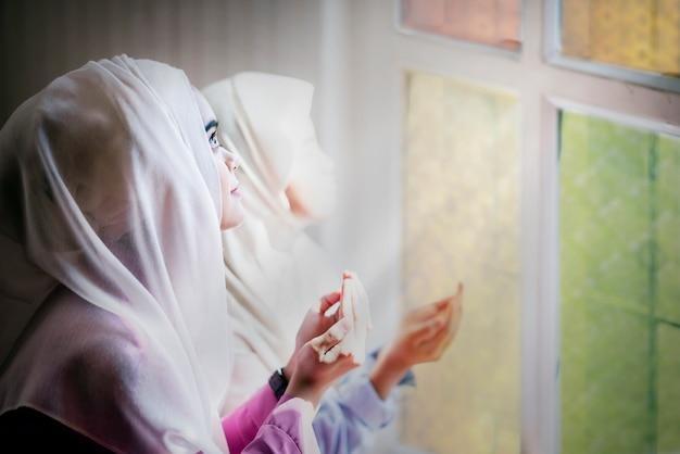 Piękne kobiety-muzułmanie modlą się o błogosławieństwo boga i duchowość przebaczenia.