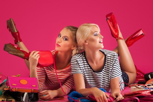 Piękne kobiety na różowej ścianie. kobiety otoczone kolorowymi torebkami, torebkami i butami.