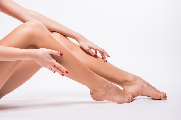 Piękne kobiety nogi z gładką białą skórą na białym tle