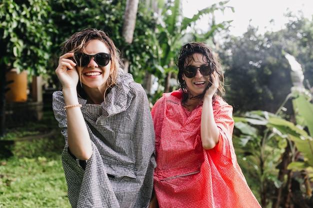 Piękne kobiety o ciemnych mokrych włosach śmieją się podczas spaceru. plenerowe zdjęcie wspaniałych kobiet w płaszczu przeciwdeszczowym podczas trekkingu.