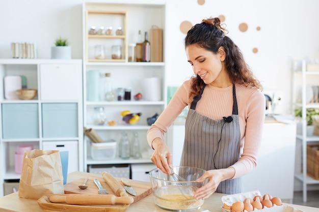 Piękne kobiety rasy kaukaskiej sobie fartuch stojących przy stole w nowoczesnej kuchni bijąc jajka w szklanej misce za pomocą bata