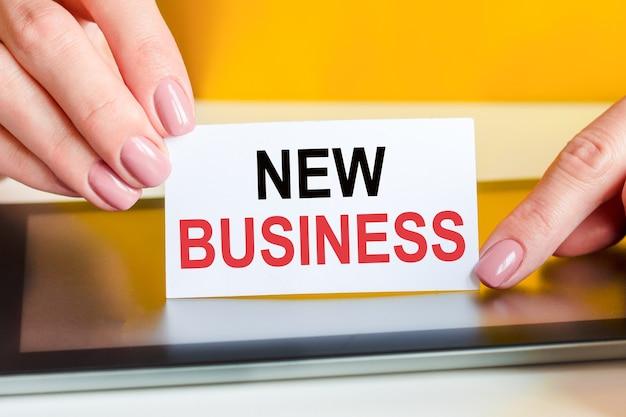 Piękne kobiety ręce trzyma kawałek białego papieru z tekstem: nowy biznes