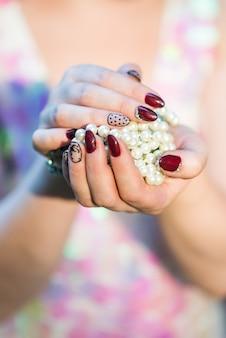 Piękne kobiety ręce trzyma perłę