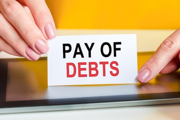 Piękne kobiety ręce trzymają kartkę białego papieru z tekstem: spłata długów. może być używany w biznesie, marketingu, koncepcji finansowej.