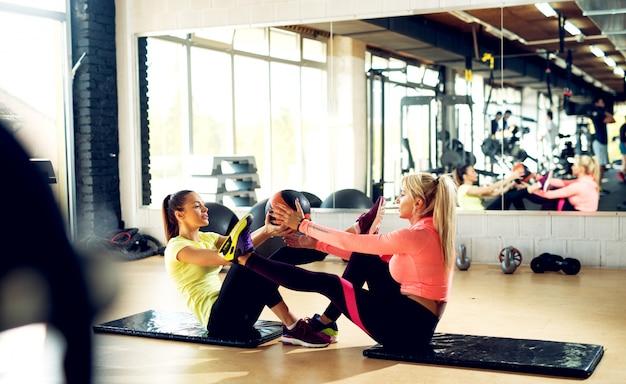 Piękne kobiety robi rozciągającym ćwiczeniom z sprawności fizycznej piłką w gym.