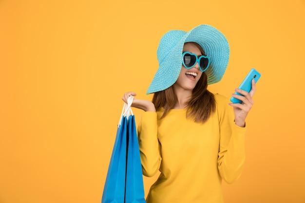 Piękne kobiety robią zakupy latem z niebieskimi papierowymi torbami
