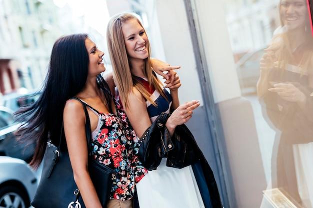 Piękne kobiety robiące zakupy na świeżym powietrzu i patrzące na witryny sklepowe