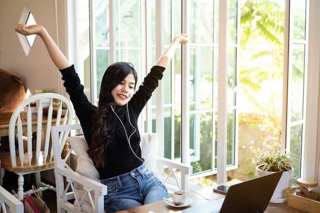 Piękne kobiety słuchające muzyki i pracujące z laptopem w kawiarni