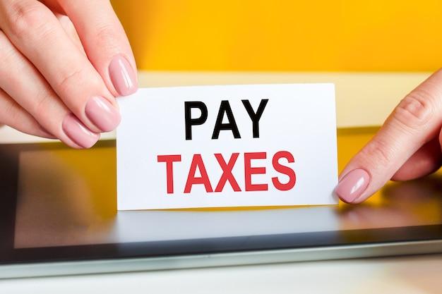 Piękne kobiety trzymają w rękach kartkę białego papieru z tekstem: płacić podatki. może być używany w biznesie, marketingu, koncepcji finansowej.