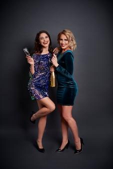 Piękne kobiety trzymając butelkę szampana i flet szampana