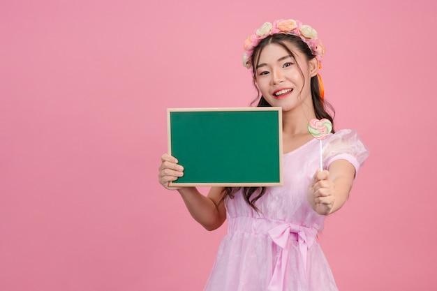 Piękne kobiety ubrane w różowe sukienki księżniczki trzymają zieloną tablicę na różu.