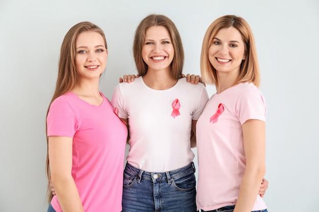 Piękne kobiety w różnym wieku z różowymi wstążkami na jasnym tle. koncepcja raka piersi