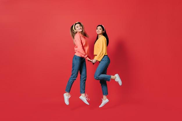 Piękne kobiety w stylowych bluzach i dżinsach skaczą po czerwonej ścianie