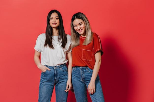 Piękne kobiety w stylowych t-shirtach i dżinsach patrzą z przodu na czerwoną ścianę