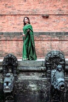 Piękne kobiety w sukience saree stojące pozujące do świętej studni w pałacu królewskim placu patan durbar.