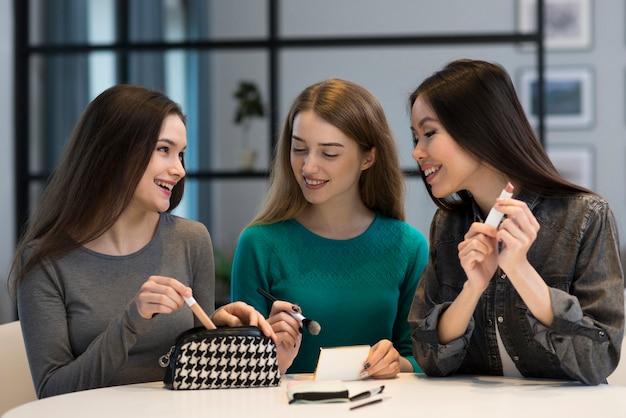 Piękne kobiety wypróbowują akcesoria do makijażu